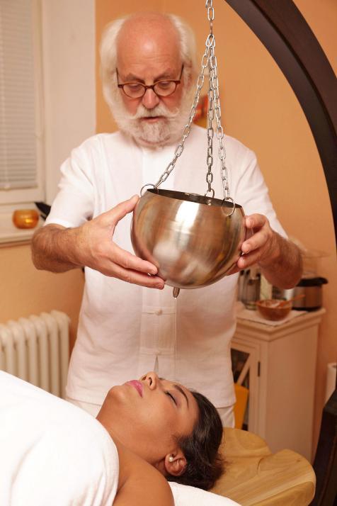 Jaruwan bekommt eine Shirodhara-Behandlung von Therapeut Holger