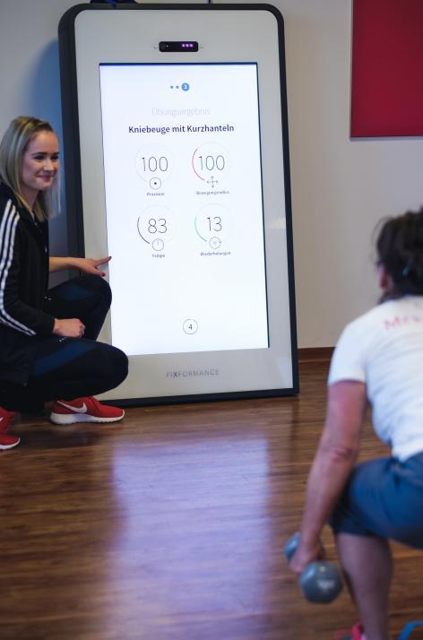 Trainerin Neele (li.) begleitet das Training eines Mitglieds am Smart Trainer