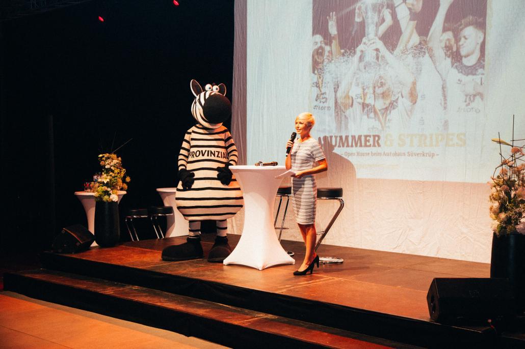 Anett Sattler moderiert regelmäßig Events. Hier führt sie beim großen Summer & Stripes Event des THW Kiel, Autohaus Süverkrüp und falkemedia durch den Abend