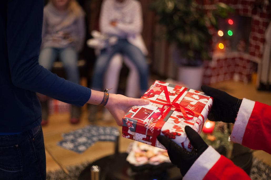 Redakteur Bastian Karkossa – äh, der Weihnachtsmann! – verteilt die liebevoll verpackten Geschenke an die Kinder