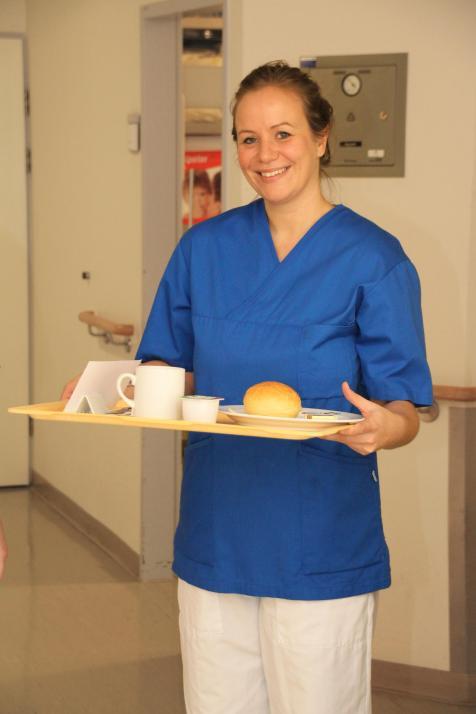 Gesa serviert den Patienten das Frühstück