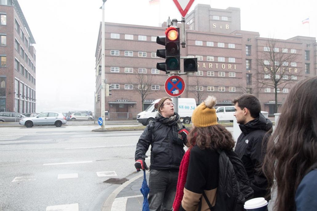 Kirk (li.) erklärt den Erasmus-Studenten, wie wichtig es in Deutschland ist, an der Ampel auf Grün zu warten