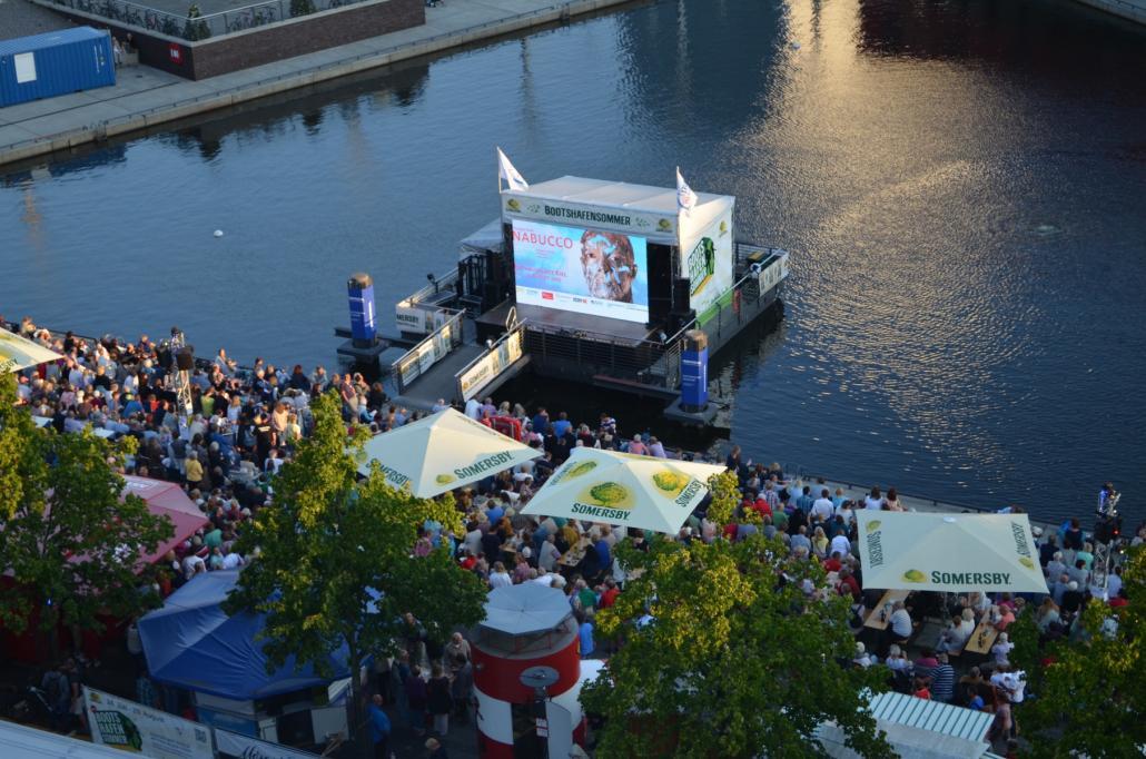 An vielen öffentlichen Orten kann man die Premiere des Sommertheaters verfolgen – so wie hier am Bootshafen