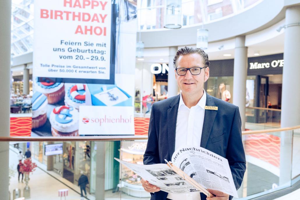 Center Manager Herr Karsten Bärschneider mit der Ausgabe der Kieler  Nachrichten vom Eröffnungstag des Sophienhof Kiel