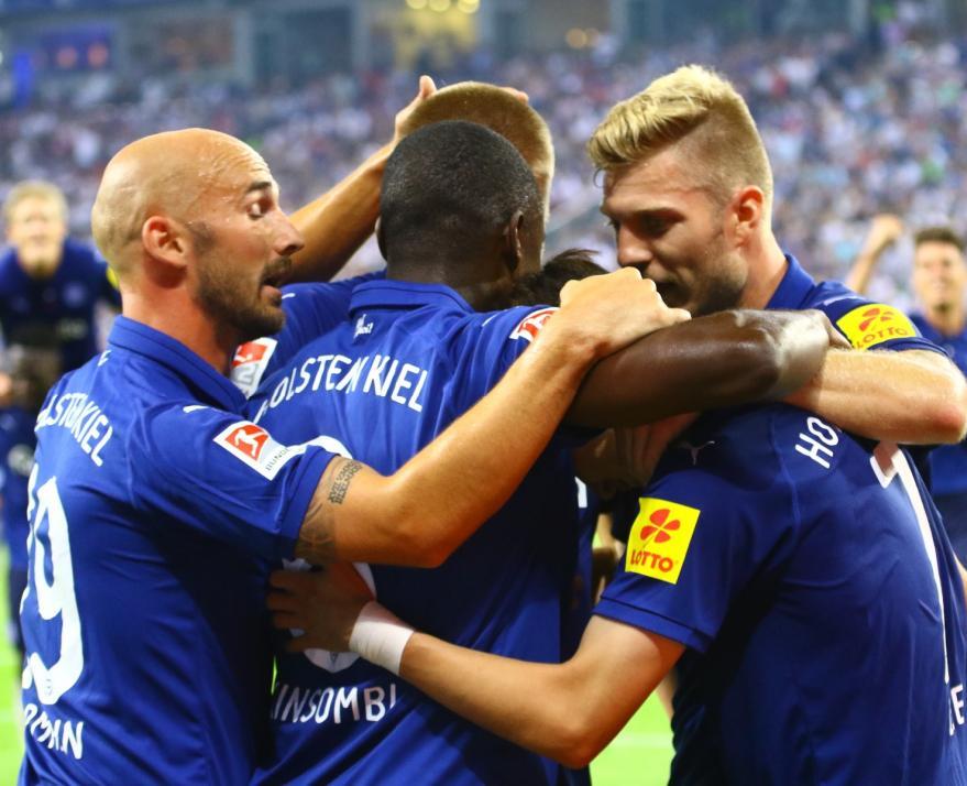 Die Kieler Spieler jubeln nach dem Auftaktsieg beim Hamburger SV