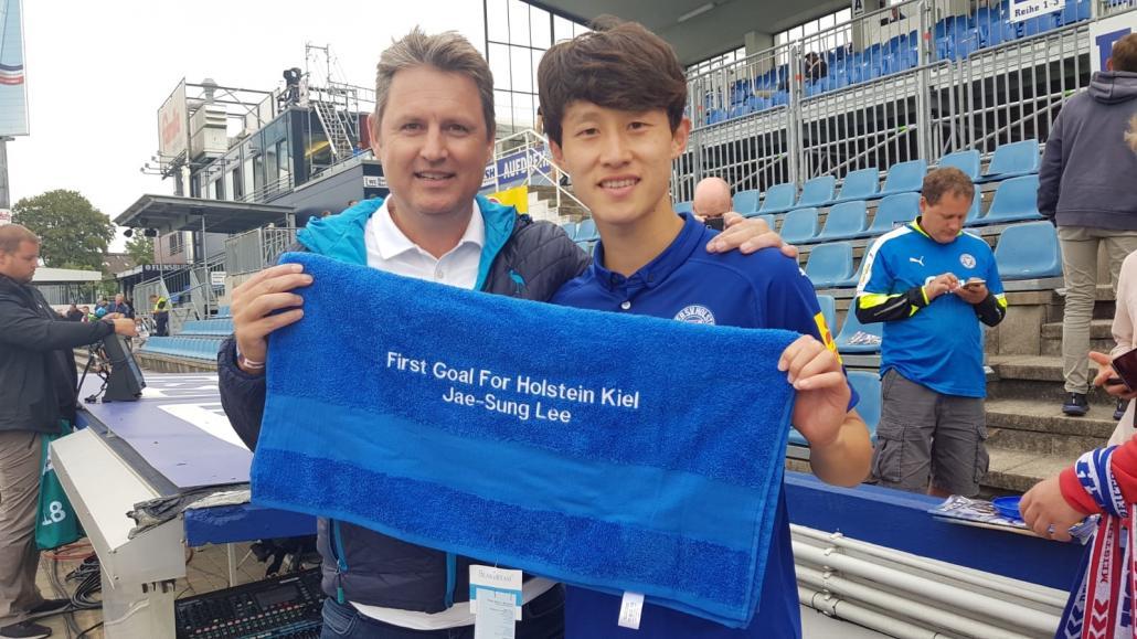 Heinrich Knievel ist Sportpartner von Holstein Kiel. Hier überreicht Geschäftsführer Thorsten Kibbel (li.) KSV-Spieler Jae Sung Lee ein Handtuch mit WidmungHeute verfügt das Traditionsunternehmen