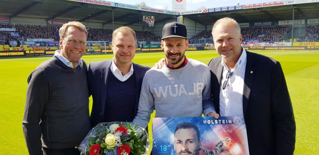 Wohlgemuth am Spielfeldrand mit Kenneth Kronholm (2. v. l.) wird von Steffen Schneekloth (Präsident), Fabian Wohlgemuth (Sportdirektor)und Wolfgang Schwenke (Vizepräsident)verabschiedet (v. l.)
