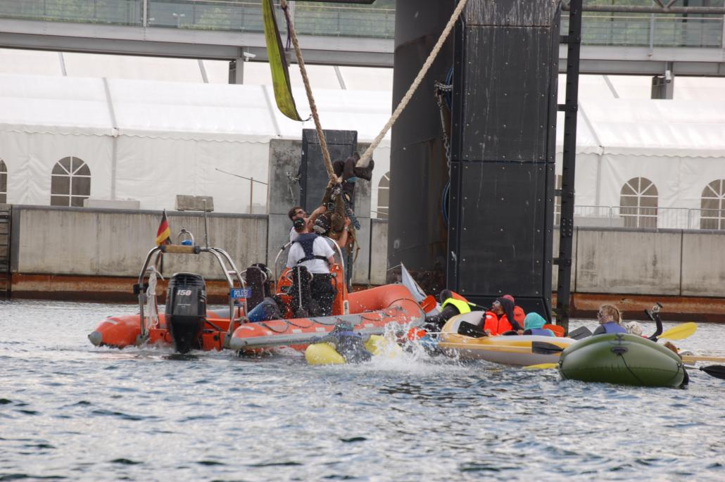 """Die Aktivisten der TurboKlimaKampfGruppe Kiel mussten von der Wasserschutzpolizei entfernt werden, damit die """"Zuiderdam"""" mit sechs Stunden Verspätung ablegen konnte"""