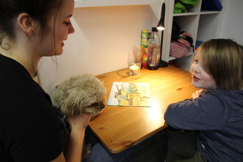 """Ergotherapeutin Julia Rathjen mit Therapiehund """"Pommes"""" und Sam beim Puzzeln"""