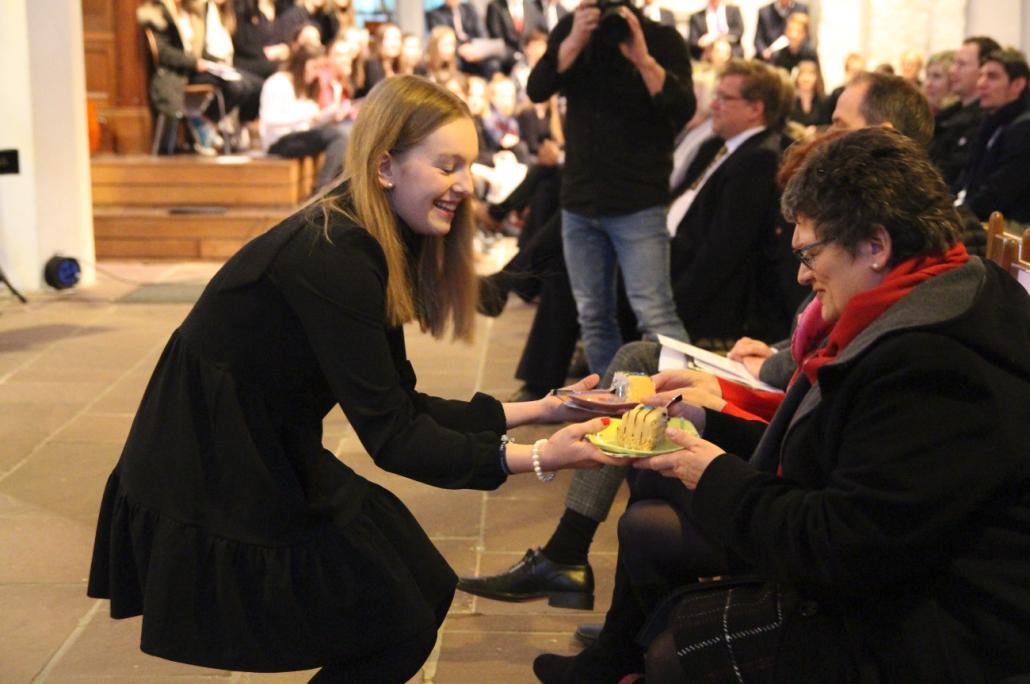 Schülersprecherin Greta Balow überreicht Bürgermeisterin Renate Treutel das symbolische Stück Geburtstagstorte