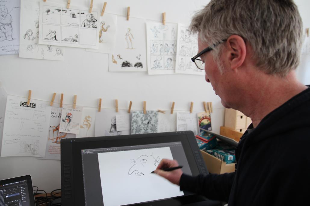 Volker Sponholz zeichnet digital an seinem Grafik Tablet und demonstriert die Vorteile des Geräts.