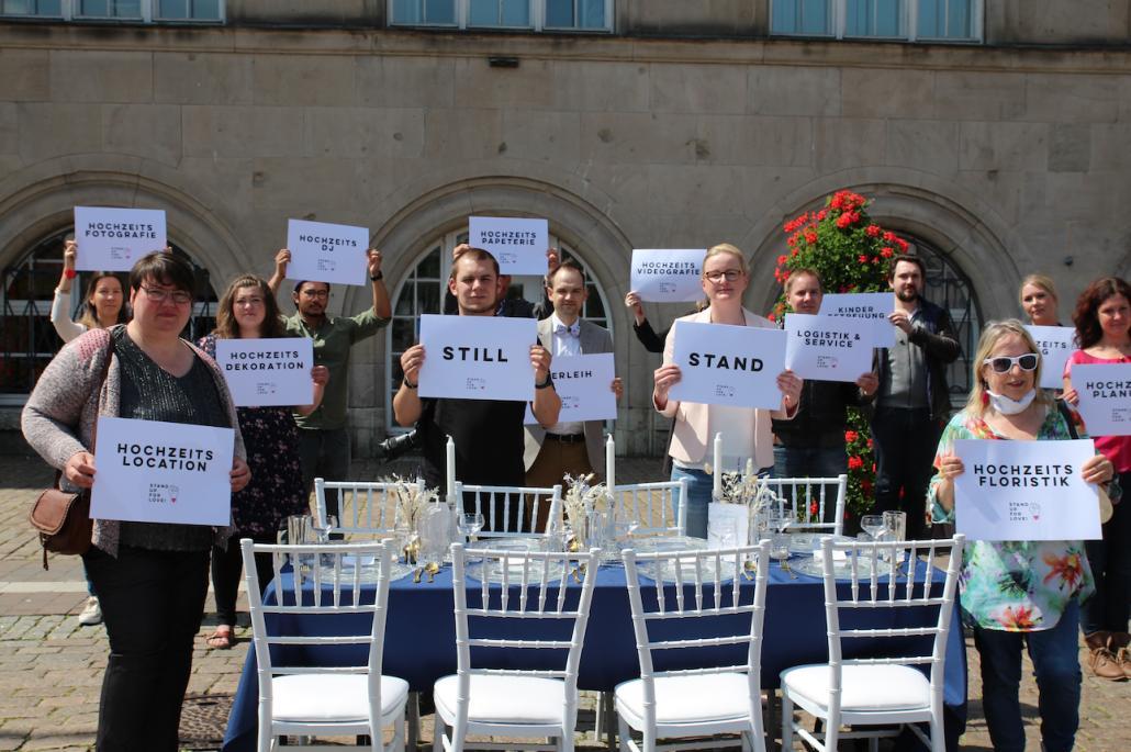Florist*innen, DJ's und Fotograf*innen stehen Seite an Seite, um für gleichberechtigten finanziellen Ausgleich zu protestieren.