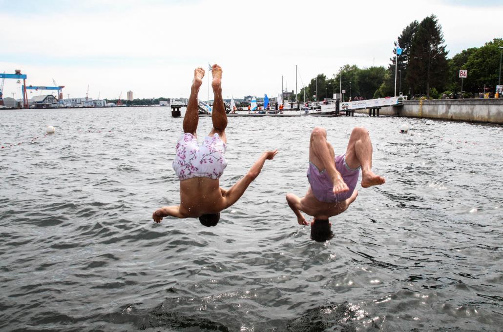 Jakob und Nils (v. li) gönnen sich den Sprung in die Kieler Förde vom Badesteg am Camp 24/7