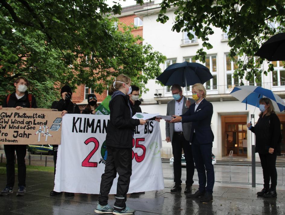 Dennys Bornhöft (FDP, 2. v. r.) nimmt das Schriftstück von Klima-Aktivistin Dorothea Lätzel entgegen.