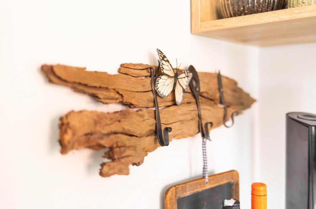 Praktische Demo aus Fundstücken: ein Holzscheit mit alten Löffeln ziert eine Küchenecke
