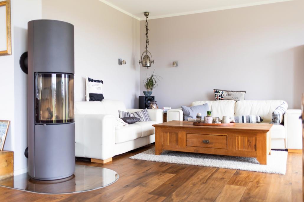Im Wohnzimmer treffen sanfte weiße Sofas auf eine robuste Industrieleuchte