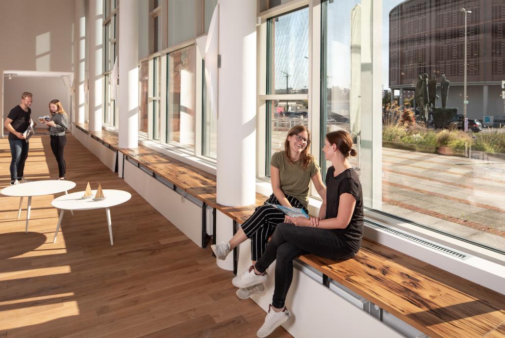 Aufgearbeitete Holzbohlen von alten demontierten Schiffsstegen dienen als Sitzfläche und unterstreichen das maritime Ambiente des Welcome Centers Kieler Förde