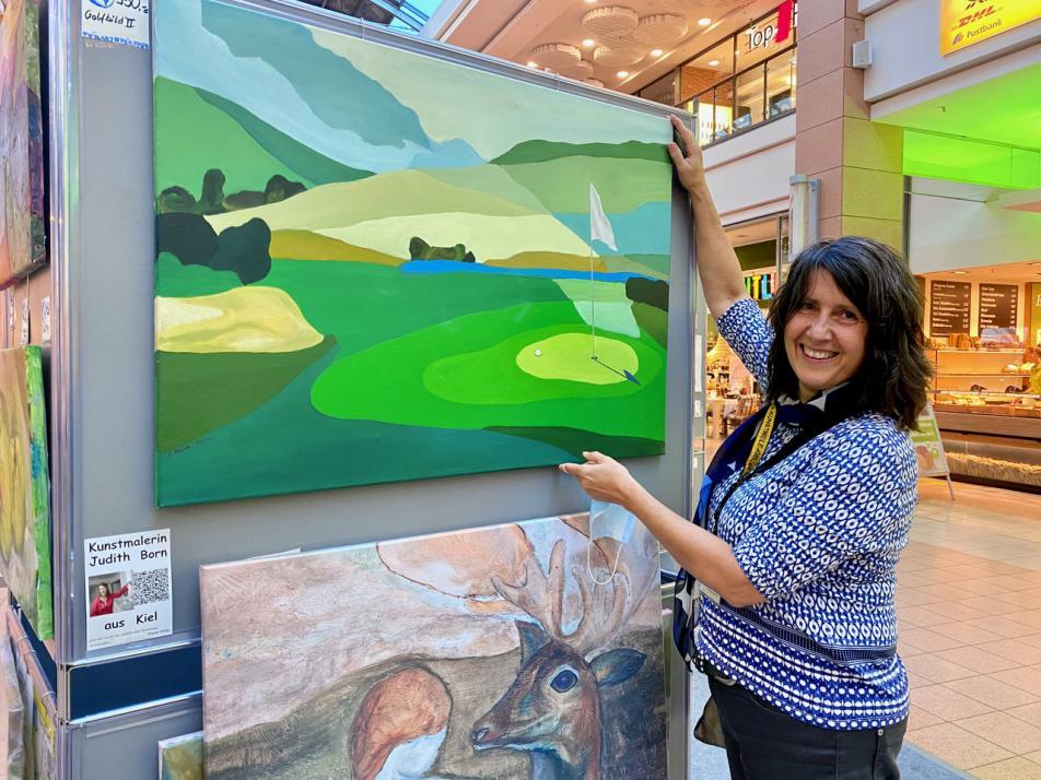 """Judith Born präsentiert ihr Gemälde """"Golfplatz"""" in der Ausstellung"""