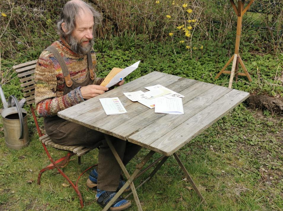 Chistian Kuhtz liest in seinem Garten in den Briefen, die er aus fernen Teilen der Erde bekommen hat.