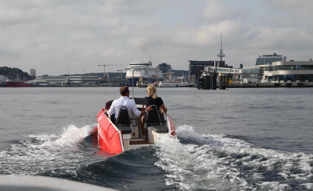 Inken Kuhl und Holger Thielen von der Förde Sparkasse fahren mit einem der E-Tretboot-Prototypen.